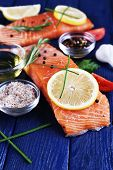 Fresh salmon with spices and lemon on wooden table