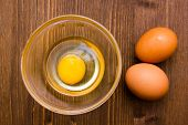 Open egg on wooden bowl on top