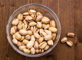 Pistachios on wooden bowl on top