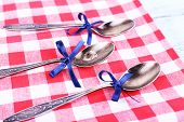 Metal spoons on checkered napkin on light blue background