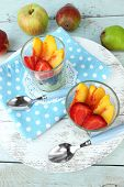 fresh tasty fruit salad on blue wooden table