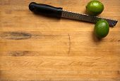Limes And Grater On A Cutting Board