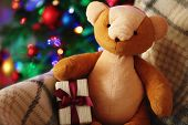Teddy bear and gift box in rocking chair on Christmas tree background