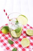 Lemonade in glass on napkin on bright background