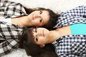 Beautiful girls twins in pajamas lie on carpet
