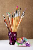 Paint brushes with paints on beige background