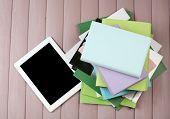 PC tablet on  top of pile of books and magazines on wooden background