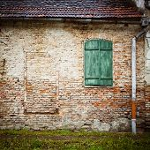 vintage brick wall background with roof, old window and rain pipe