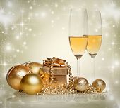 Champagne glasses and christmas decorations on sparkling background