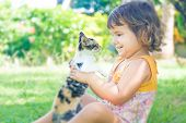 outdoor portrait of young child girl with small kitten, girl playing with cat on natural background