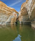 Unique canyon in the desert. Picturesque canyon En-Avdat in the Negev desert. Bowl waterfall reflects the sky. Sandstone canyon walls form round bowl