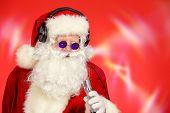 Modern Santa Claus in headphones and sunglasses. DJ, party. Christmas celebration.