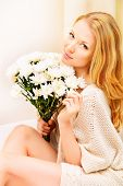 Pretty young woman sitting on a sofa at home, holding white flowers and smiling. Interior.