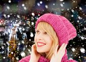 happiness, winter holidays, christmas and people concept - smiling young woman in pink hat and scarf over blue snowy background