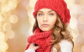 happiness, winter holidays, christmas and people concept - close up of young woman in red hat and scarf over beige lights background