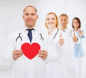 medicine, charity, gesture and healthcare concept - smiling doctor with red heart and stethoscope over group of medics showing thumbs up