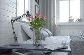 stock photo of vase flowers  - Pretty vase of fresh pink roses in a modern bedroom interior standing alongside an anglepoise lamp on the bedside table - JPG