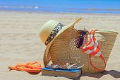 pic of sunbather  - sunbathing accessories on sandy beach in straw bag - JPG