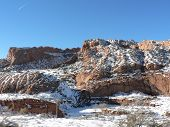 stock photo of fallen  - Snow has fallen on the rocks and the sun warms the ground to melt the snow - JPG