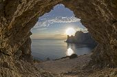 stock photo of grotto  - View from a small grotto on an evening sun setting behind the coastal cliffs - JPG
