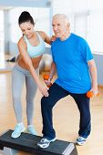 picture of geriatric  - Full length of confident female physical therapist working with senior man in health club