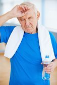 picture of forehead  - Tired senior man with towel on shoulders keeping eyes closed and touching forehead while standing in health club - JPG