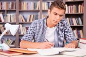foto of concentration man  - Confident young man making research while sitting in library - JPG