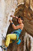 pic of climbing wall  - female rock climber climbs on a rocky wall - JPG