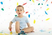 stock photo of floor covering  - Adorable 3 year old boy child creatively stains on the wall floor with colourful paint - JPG
