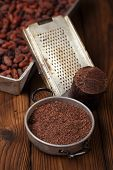 picture of cocoa beans  - grated dark chocolate in tin with cocoa beans and solid piece in old texured wood - JPG