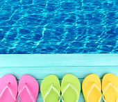 picture of beside  - Colored flip flops on wooden platform beside sea - JPG