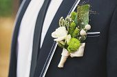 pic of boutonniere  - Very beautiful buttonholes on the jacket of a young and handsome groom - JPG