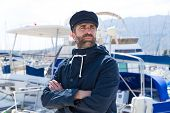 foto of marina  - Sailor man in marina port with boats background and blue cap - JPG