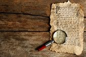 picture of hieroglyph  - Grunge paper with hieroglyphics with magnifier on wooden background - JPG