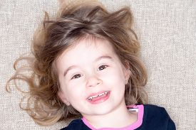 foto of vivacious  - Pretty vivacious three year old little girl lying on a carpet with her hair flying around her face smiling happily up at the camera with a joyful expression - JPG
