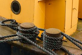 image of safe haven  - Old boat secured with knotted black ropes - JPG