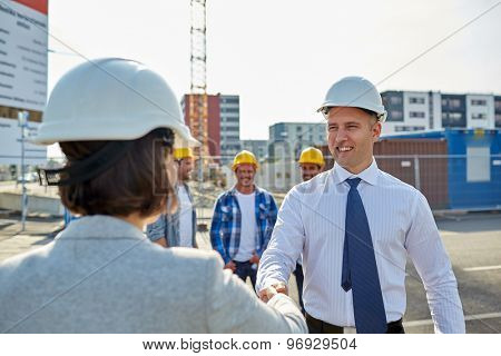 business, building, teamwork, gesture and people concept - group of smiling builders or architects i