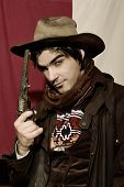 stock photo of wild west  - handsome boy in cowboy clothes with weapon - JPG
