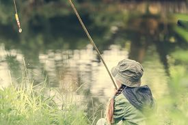 pic of rod  - little fisher girl holds a rod sitting near a river - JPG