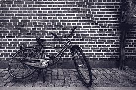 picture of monochromatic  - Unique classic vintage hipster bicycle leaning against the street wall in urban downtown setting cyclcing and healthy lifestyle concept black and white monochromatic instagram like retro toned image - JPG