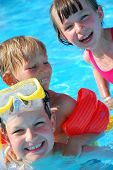 foto of happy kids  - Happy kids playing and having fun together in the pool - JPG