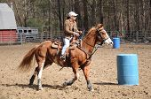 foto of barrel racing  - A young woman turns around a barrel and heads to the finish line - JPG