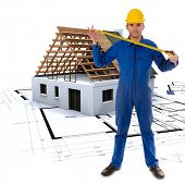 Worker extending a tape measure with a house in construction and architecture plans in the background