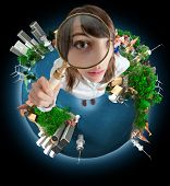 Young woman with a magnifying glass standing on the Earth