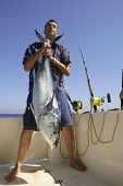 Angler fishing big game bluefin tuna on Mediterranean saltwater