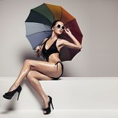 Beautiful woman in stylish black swimwear and sunglasses holding colorful umbrella. Perfect slim tan poster