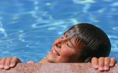 Young Boy Enjoying The Sun In A Swimming Pool
