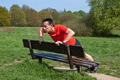 Man exercising doing pressups on a Park Bench