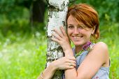 Smiling Girl Embrace A Birch Tree