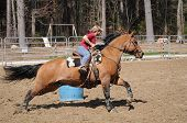 pic of barrel racing  - A young woman turns around a barrel and races to the finish line - JPG